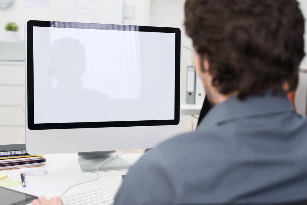 パソコンを見る男の後ろ姿