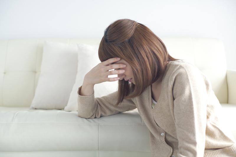 体調不良で頭に手を当てる女性