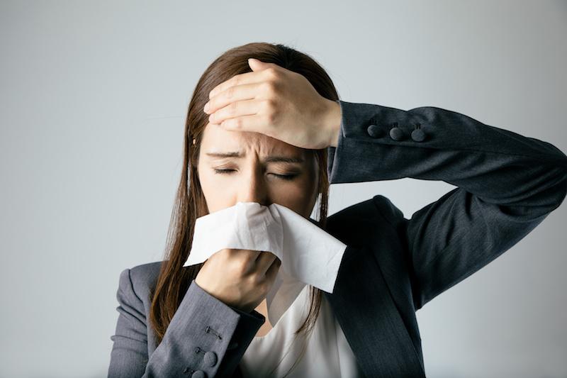 鼻づまりと頭痛に悩まされる女性