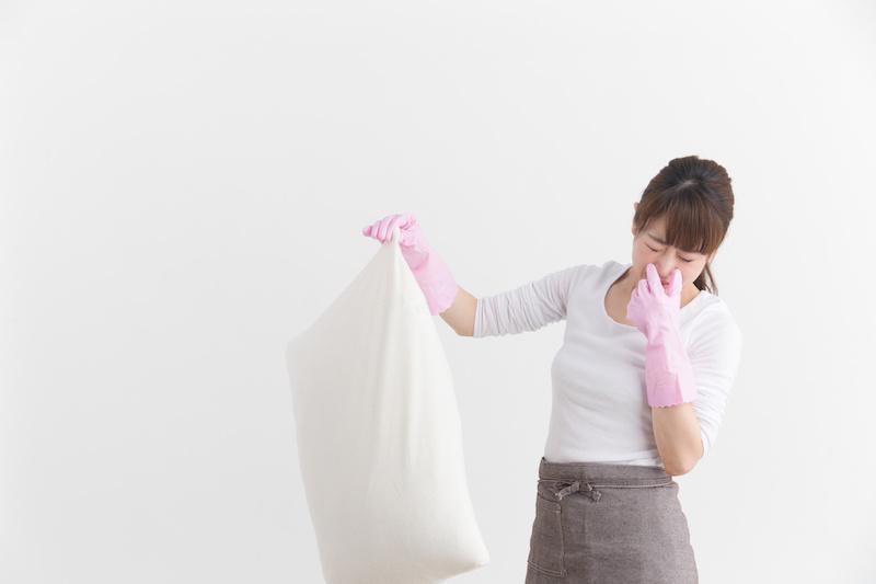 臭い枕をつまむ女性